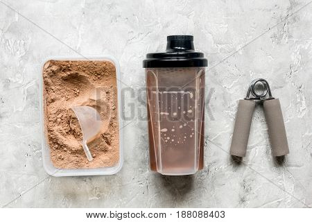 Fitness nutrition with shaker, bars on stone table background top view