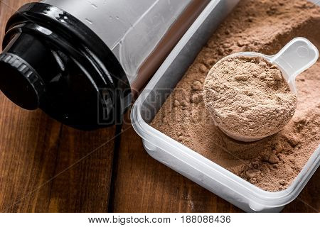 Fitness nutrition with scoop and shaker on wooden table background