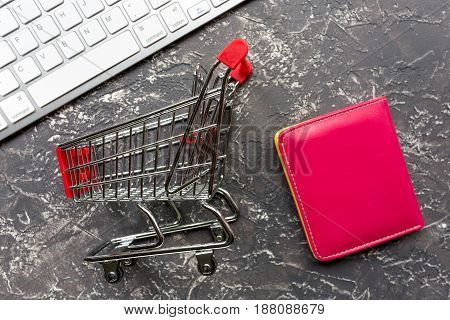 office desk with mini trolley and wallet for online buying on dark background top view