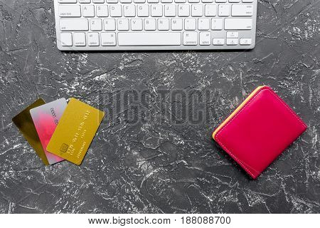buying products with credit cards and keyboard on dark table background top view space for text