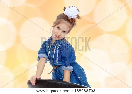 The little blonde girl with a large white bow on the head and short denim dress.She poses on a revolving chair.Brown festive, Christmas background with white snowflakes, circles.