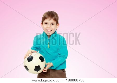 Little boy in brown pants and blue shirt playing with a soccer ball.From fun boy laughs out loud.Pale pink gradient background.