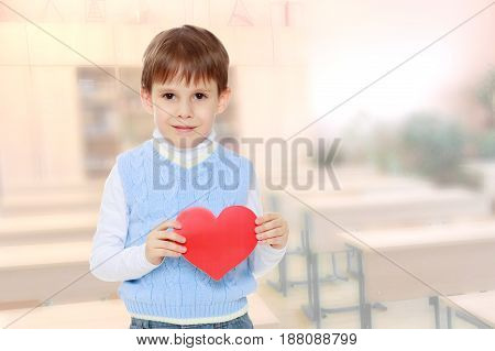 Cute little boy holds in his hands a heart . Close-up.During a lesson in school.