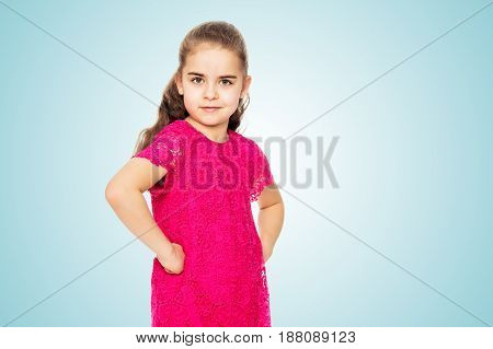 A beautiful little girl of primary school age, with long flowing hair, in a bright red dress.She is posing in front of the camera, holding hands in the ribs. Close-up.On the pale blue background.