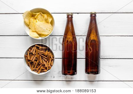 cinema and TV whatching with beer, crumbs, chips on white wooden background top view