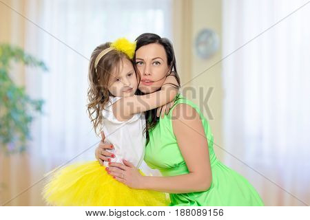 Beautiful young mother in a short green dress and her little beloved daughter in a yellow skirt.Daughter gently hugs the mother's neck.In the children's room.