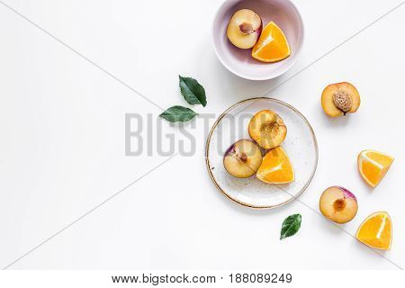 tropical peach and orange fruits for fresh summer juice on plates on white table background top view space for text