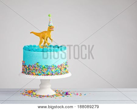 Blue buttercream birthday cake with colorful sprinkles and toy dinosaur over a light grey background.