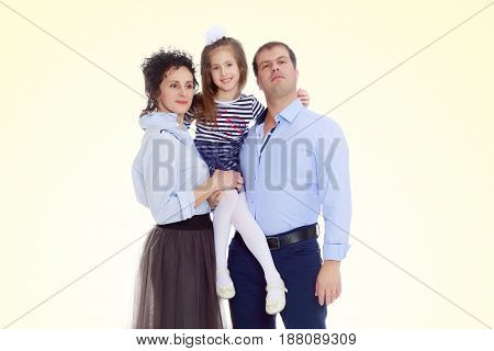 Happy young family, mom dad and little daughter.Parents keep the girl in her arms , and she hugs their neck.On a yellow gradient background.