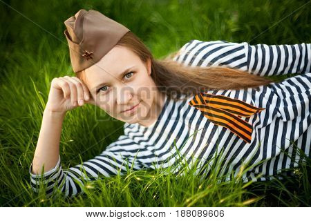 Girl In Uniform Of The Great Patriotic War. Warrior Sitting On The Grass Between Flowers. Girl Weari