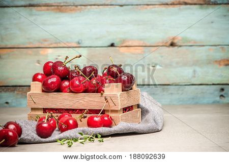 Red Ripe Cherries In Small Wooden Box