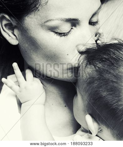 young brunette happy mother holding toddler baby son, breast-feeding concept, lifestyle modern people kissing