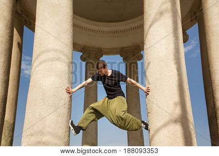 Young man climbs up honey columns. Parkour in the urban space. Sport in the city. Sport Activities outdoors. Acrobatics