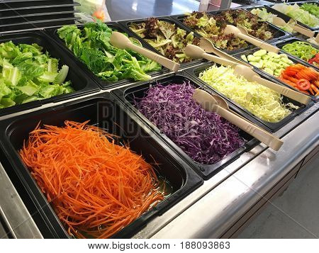 Close up salad bar with various fresh vegetables at supermarket.