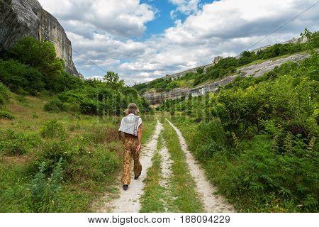 Tourist walks by Cave City in Cherkez-Kermen Valley, Crimea