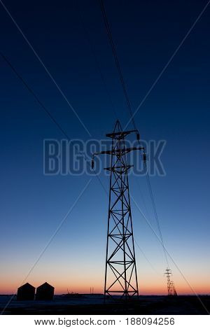 Vertical format of Transmission Tower Silhouetted at Sunset