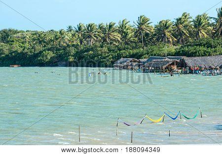 Jericoacoara Ceara state Brazil - July 2016: tourists and hammocks are on the beach and Lagoon Tatajuba from above