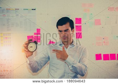 Young businessman with a clock in the background office.