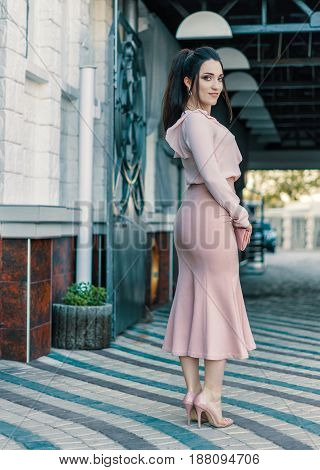 young beautiful stylish woman in the street. She is wearing pink Skirt and blouse