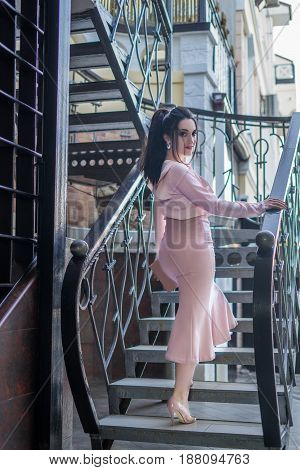 young beautiful stylish woman on the ladder. She is wearing pink Skirt and blouse