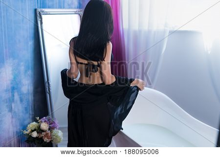 Woman in bath. Back view of Sexy brunette woman taking off her clothes before bath. She is wearing black sexual lingerie