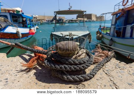 Rusty bitt with ropes on the berth. Moored fishing boats in the background.
