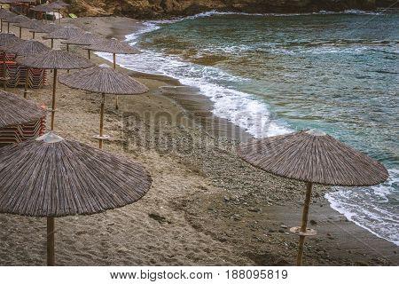 Straw umbrellas on the deserted evening beach. Stylization. Toning. Stylization. Toning.