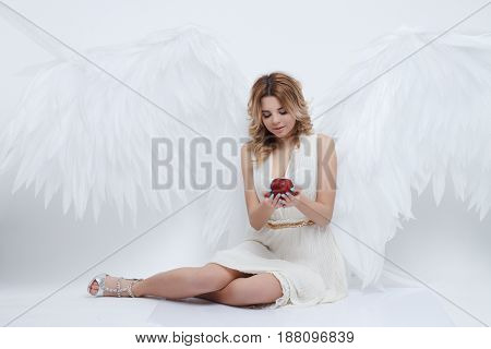 beautiful young model with big angel wings sitting in the studio and holding red apple of discord and looking at it. white background.