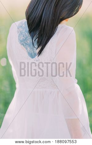 The close-up back view of the bride in the white dress with the open shoulders and back in the green spring field. The tattoo on the back