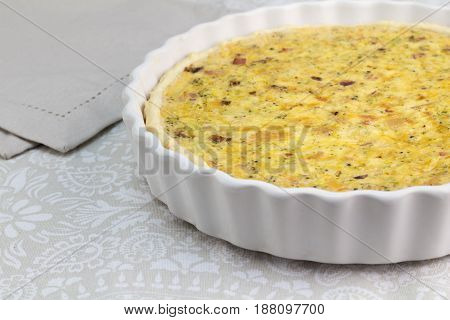 Creamy quiche with cheese bacon and mushroom - Open pie in white dish with selective focus - food background with text space