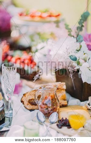 The composition of the wedding table setting. The table is full of beautiful flowers in the wooden pot, tasty cheese, nicely smelling bread, fruit cakes and dried fruit