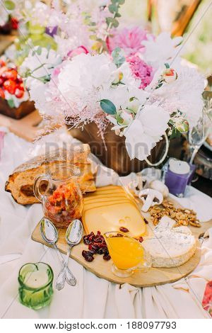 The above view on the wedding table setting. The composition of the fresh cheese, smelling bread, tasty dried fruit and awesome fruit cake is surrounded by little candles and flowers in the wooden pot