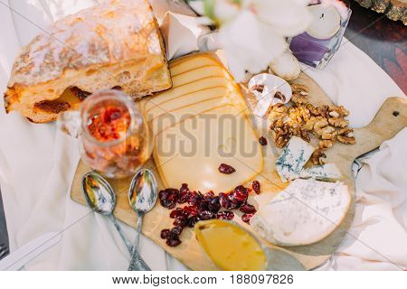 Close-up portrait of delicious food. The composition of cheese, bread, mushrooms, dried fruits, nuts and jar on the wooden stand