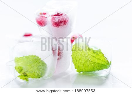 ice cubes with fresh red berries and mint leaves on white table background
