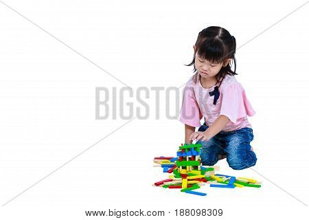 Alone child messily playing educational toy wood blocks. Sad asian girl crying and seem unhappy. Isolated on white background. Free form copy space.