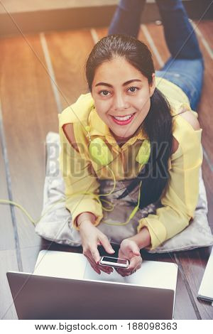 Smiling Asian Woman Using Laptop Computer With Earphones.