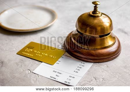 restaurant bill, credit card and waiter ring on stone table background