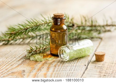 spa and aromatherapy with organic spruce oil and sea salt in glass bottles on wooden table background