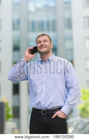 Young businessman talking on his phone outdoors.