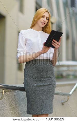 Happy business woman using tablet pc in front of office building.