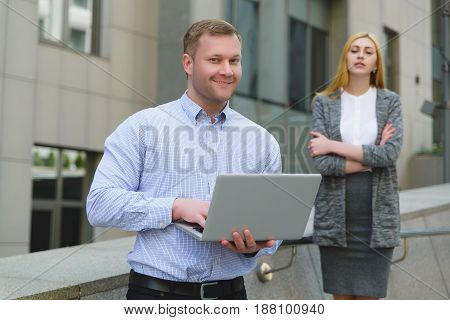 Happy businessman with laptop ahead of businesswoman who looks at screen outdoor.