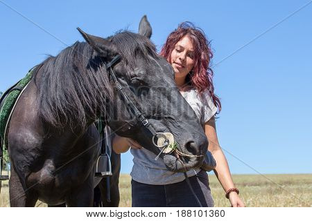Portrait of young beautiful woman with black horse in nature. Kiev Ukraine