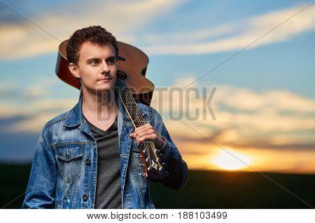 Teenage Boy Playing Guitar At Sunset