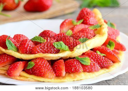 Sweet strawberry omelette. Delicious omelette stuffed with strawberries and garnished with mint leaves on a plate. Healthy and tasty breakfast or lunch idea for kids. Closeup