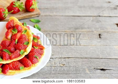 Easy stuffed omelette. Healthy and quick omelette stuffed with fresh strawberries and garnished with mint on a plate and wooden background with copy space for text. Strawberry omelette breakfast