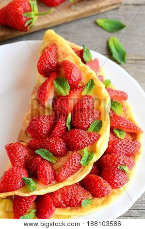 Sweet stuffed omelet. Delicious omelet stuffed with strawberries and garnished with mint leaves on a plate. Favorite breakfast recipe for kids. Strawberry dessert. Vertical photo. Closeup