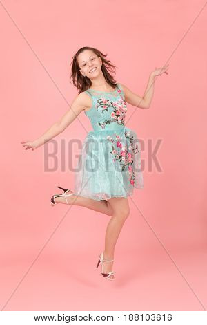Cheerful jumping girl on a pink background