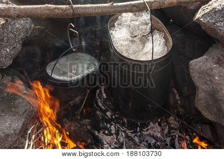 Two tourist pot over the fire in the camp