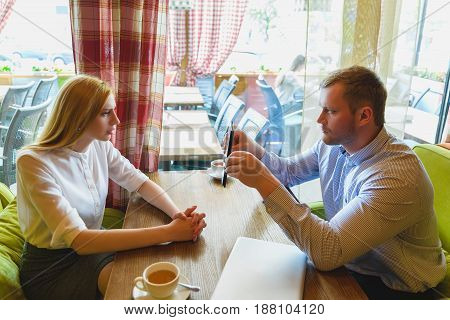 Business meeting in a cafe. Disgruntled man shows a tablet to woman.