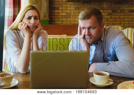Man and woman Looking at the laptop. They are saddened and distressed.
